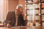 Senior businessman thinking while going through paperwork in the office.